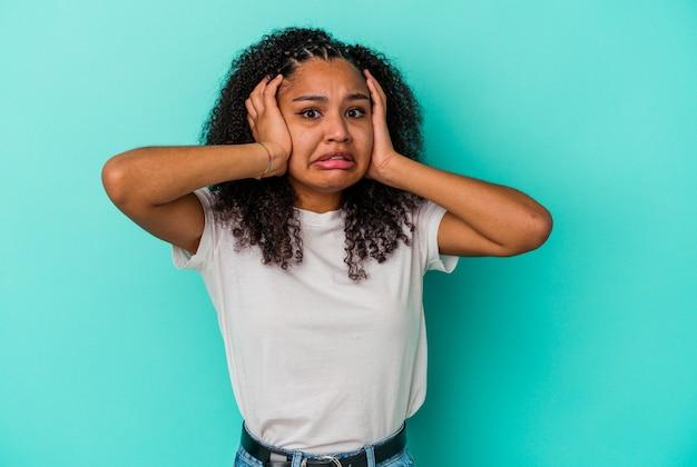 Jonge afrikaanse amerikaanse vrouw die op blauwe achtergrond wordt geïsoleerd huilen, ongelukkig met iets, ondraaglijke pijn en verwarringconcept.