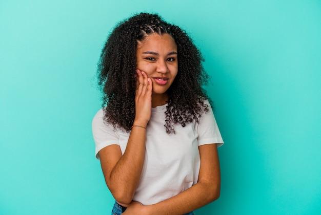 Jonge afrikaanse amerikaanse vrouw die op blauwe achtergrond wordt geïsoleerd met een sterke tandenpijn, kiespijn.