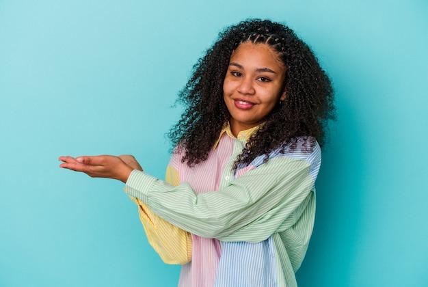 Jonge afrikaanse amerikaanse vrouw die op blauwe muur wordt geïsoleerd die een exemplaarruimte op een palm houdt.