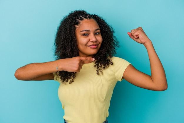 Jonge afrikaanse amerikaanse vrouw die op blauwe muur wordt geïsoleerd die krachtgebaar met wapens, symbool van vrouwelijke macht toont