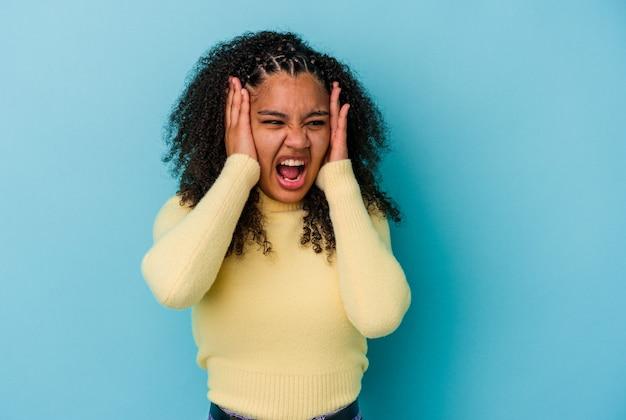Jonge afrikaanse amerikaanse vrouw die op blauwe muur wordt geïsoleerd die oren behandelt met handen die niet te hard geluid proberen te horen.