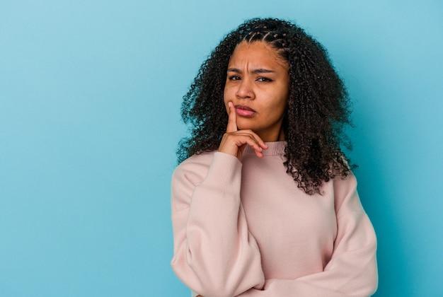 Jonge afrikaanse amerikaanse vrouw die op blauwe muur wordt geïsoleerd die zijwaarts met twijfelachtige en sceptische uitdrukking kijkt.