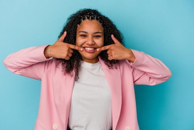 Jonge afrikaanse amerikaanse vrouw die op blauwe muur wordt geïsoleerd glimlacht, wijzende vingers naar mond.