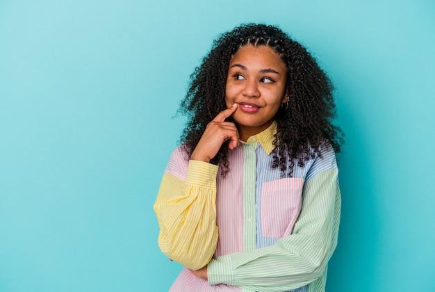 Jonge afrikaanse amerikaanse vrouw die op blauwe muur wordt geïsoleerd ontspant denkend over iets dat een exemplaarruimte bekijkt.