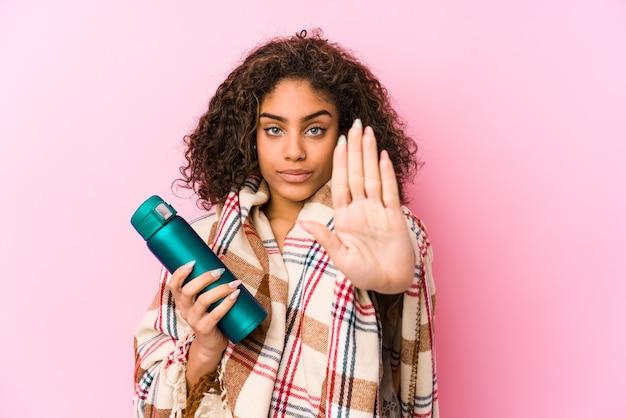 Jonge afrikaanse amerikaanse vrouw die op een geïsoleerde camping rust die zich met uitgestrekte hand bevindt die stopbord toont, dat u verhindert.