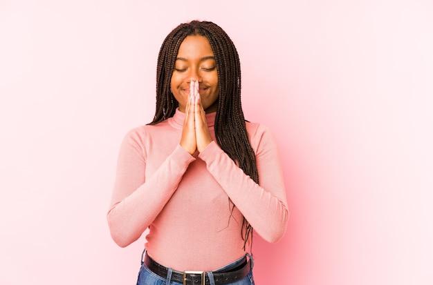 Jonge afrikaanse amerikaanse vrouw die op een roze achtergrond wordt geïsoleerd die hand in hand bidt dichtbij mond, voelt zich zelfverzekerd.