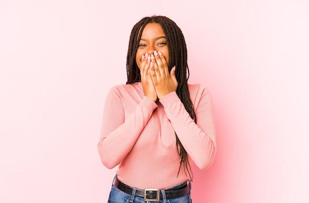 Jonge afrikaanse amerikaanse vrouw die op een roze achtergrond wordt geïsoleerd die over iets lacht, die mond behandelt met handen.