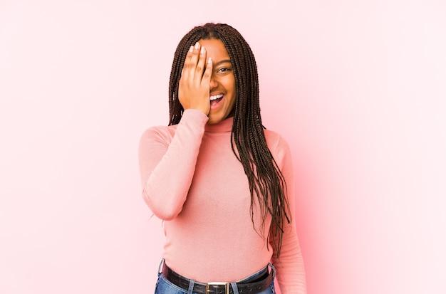 Jonge afrikaanse amerikaanse vrouw die op een roze muur wordt geïsoleerd die pret heeft die de helft van gezicht bedekt met palm.