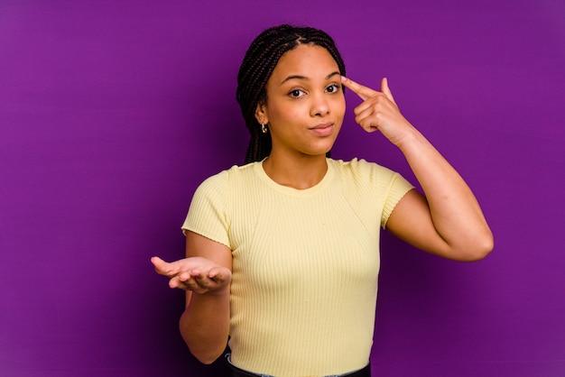 Jonge afrikaanse amerikaanse vrouw die op geel wordt geïsoleerd dat en een product bij de hand toont.