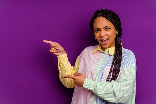 Jonge afrikaanse amerikaanse vrouw die op gele achtergrond met wijsvingers wordt geïsoleerd die een exemplaarruimte richt, opwinding en verlangen uitdrukken.