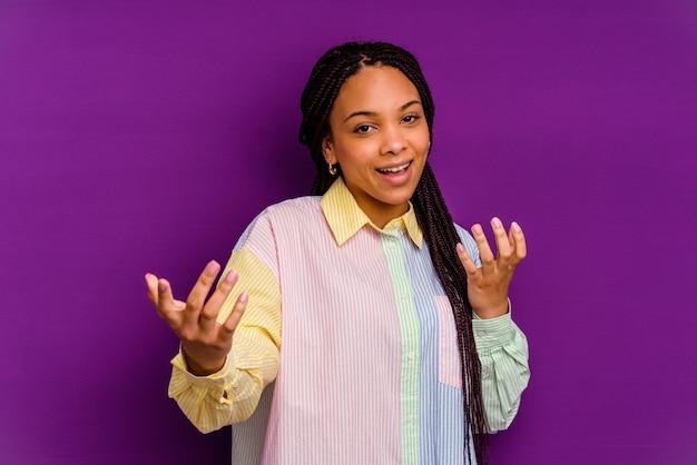 Jonge afrikaanse amerikaanse vrouw die op gele achtergrond wordt geïsoleerd die met vinger naar u richt alsof uitnodigend kom dichterbij.