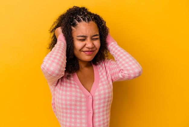 Jonge afrikaanse amerikaanse vrouw die op gele achtergrond wordt geïsoleerd die oren behandelt met handen.