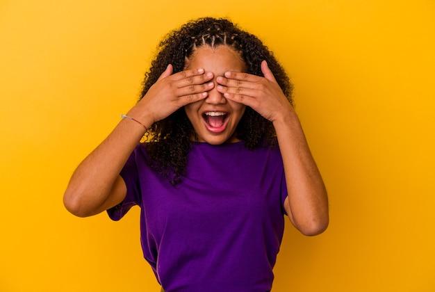 Jonge afrikaanse amerikaanse vrouw die op gele muur wordt geïsoleerd behandelt ogen met handen, glimlacht in het algemeen wachtend op een verrassing.