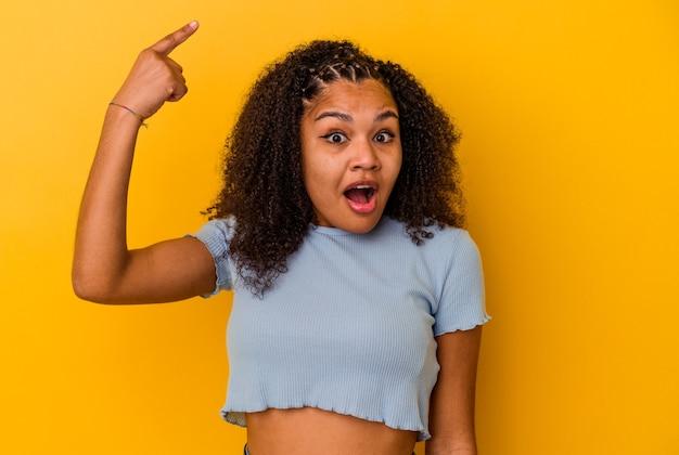 Jonge afrikaanse amerikaanse vrouw die op gele muur wordt geïsoleerd die een geweldig idee, concept van creativiteit heeft.