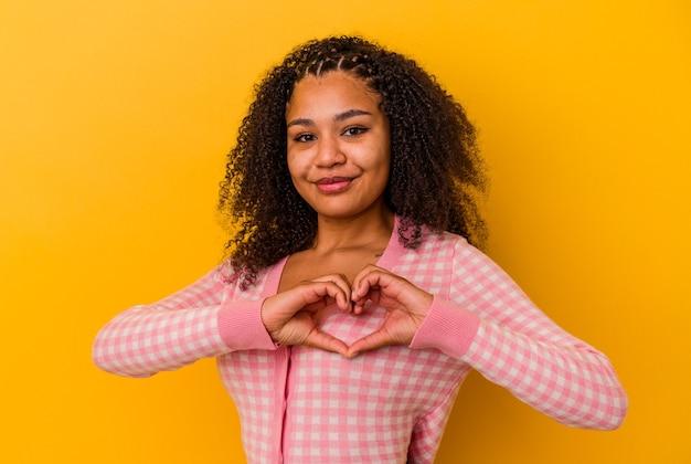 Jonge afrikaanse amerikaanse vrouw die op gele muur wordt geïsoleerd die en een hartvorm met handen glimlacht toont.