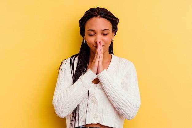 Jonge afrikaanse amerikaanse vrouw die op gele muur wordt geïsoleerd die hand in hand bidt dichtbij mond, voelt zich zelfverzekerd.