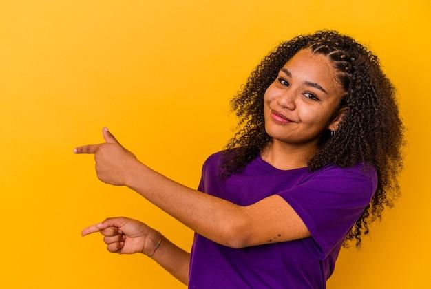 Jonge afrikaanse amerikaanse vrouw die op gele muur wordt geïsoleerd die met wijsvingers naar een exemplaarruimte richt, opwinding en verlangen uitdrukt.