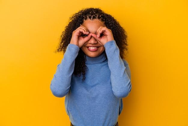 Jonge afrikaanse amerikaanse vrouw die op gele muur wordt geïsoleerd die ok teken over ogen toont