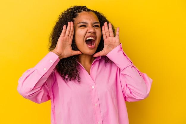 Jonge afrikaanse amerikaanse vrouw die op gele muur wordt geïsoleerd die opgewonden aan voorzijde schreeuwt.