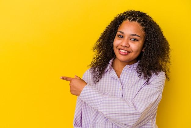 Jonge afrikaanse amerikaanse vrouw die op gele muur wordt geïsoleerd die opzij glimlacht richt en iets op lege ruimte toont.