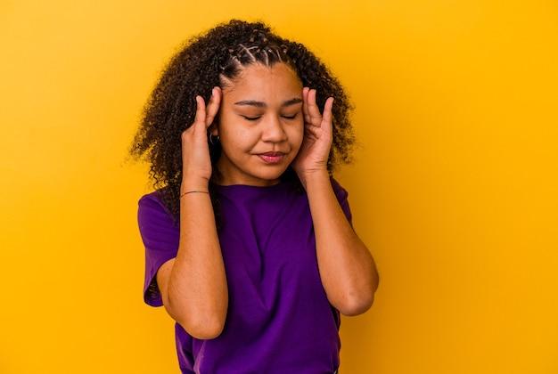 Jonge afrikaanse amerikaanse vrouw die op gele muur wordt geïsoleerd die tempels aanraakt en hoofdpijn heeft.