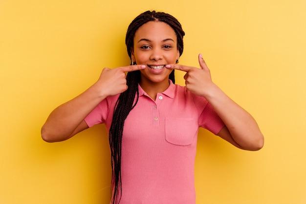Jonge afrikaanse amerikaanse vrouw die op gele muur wordt geïsoleerd glimlacht, wijzende vingers naar mond.