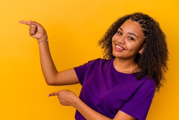 Jonge afrikaanse amerikaanse vrouw die op gele muur wordt geïsoleerd opgewonden wijzend met wijsvingers weg.