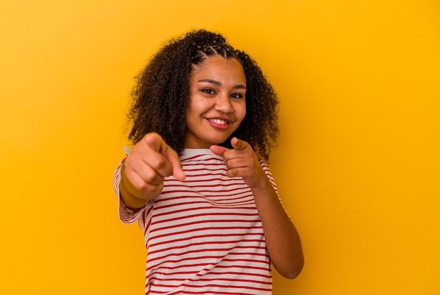 Jonge afrikaanse amerikaanse vrouw die op gele muur wordt geïsoleerd vrolijke glimlachen die naar voorzijde wijzen.