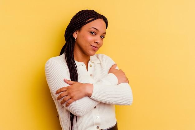 Jonge afrikaanse amerikaanse vrouw die op gele muuromhelzingen wordt geïsoleerd, onbezorgd en gelukkig glimlachen.