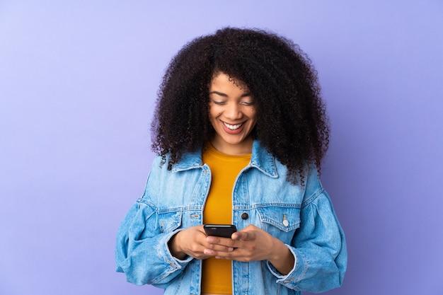 Jonge afrikaanse amerikaanse vrouw die op paars wordt geïsoleerd die een bericht met mobiel verzendt