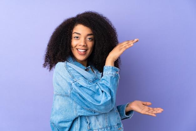 Jonge afrikaanse amerikaanse vrouw die op purpere holding copyspace wordt geïsoleerd om een advertentie op te nemen