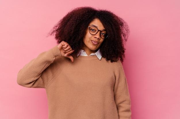 Jonge afrikaanse amerikaanse vrouw die op roze achtergrond wordt geïsoleerd die een afkeergebaar toont, duimen naar beneden. meningsverschil concept. Premium Foto
