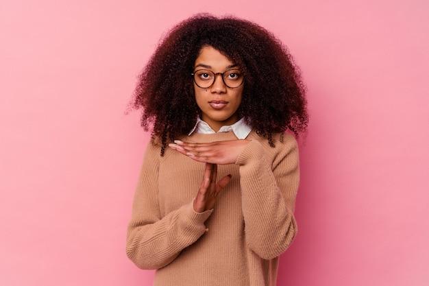 Jonge afrikaanse amerikaanse vrouw die op roze achtergrond wordt geïsoleerd die een time-outgebaar toont.