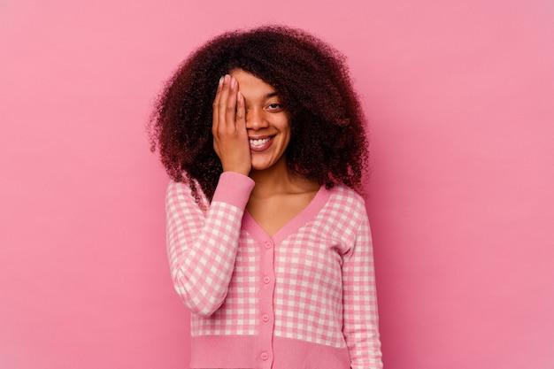 Jonge afrikaanse amerikaanse vrouw die op roze achtergrond wordt geïsoleerd die pret heeft die de helft van het gezicht bedekt met palm.