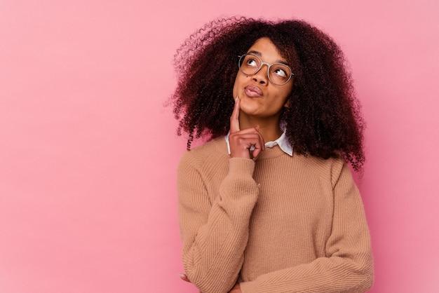 Jonge afrikaanse amerikaanse vrouw die op roze achtergrond wordt geïsoleerd die zijwaarts met twijfelachtige en sceptische uitdrukking kijkt.
