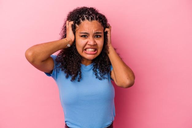 Jonge afrikaanse amerikaanse vrouw die op roze achtergrond wordt geïsoleerd huilen, ongelukkig met iets, ondraaglijke pijn en verwarringconcept.