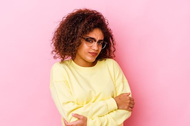 Jonge afrikaanse amerikaanse vrouw die op roze muur verdacht, onzeker wordt geïsoleerd, u onderzoekt.