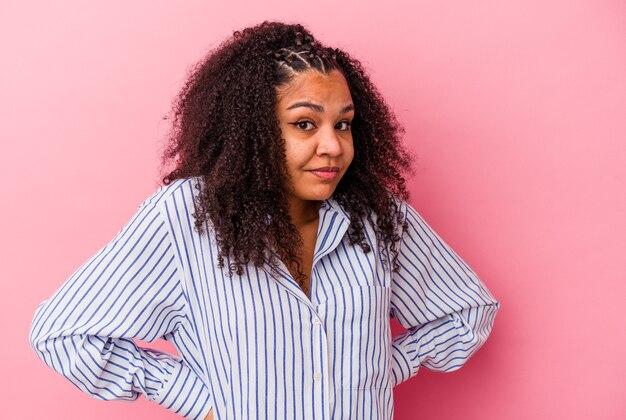 Jonge afrikaanse amerikaanse vrouw die op roze muur wordt geïsoleerd die verward, twijfelachtig en onzeker voelt.