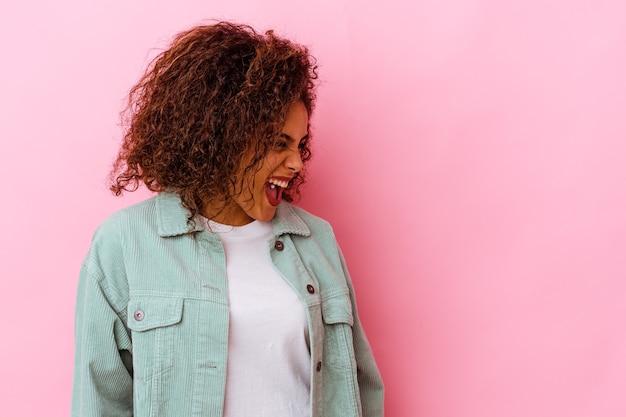 Jonge afrikaanse amerikaanse vrouw die op roze muur wordt geïsoleerd die zeer boos, gefrustreerd woedeconcept schreeuwt.