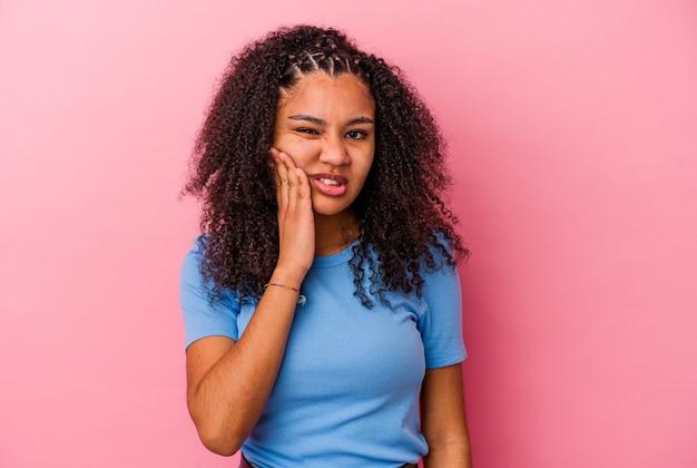 Jonge afrikaanse amerikaanse vrouw die op roze muur wordt geïsoleerd met een sterke tandenpijn, kiespijn