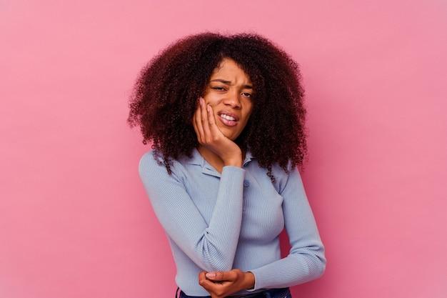 Jonge afrikaanse amerikaanse vrouw die op roze wordt geïsoleerd met een sterke tandenpijn, kiespijn.