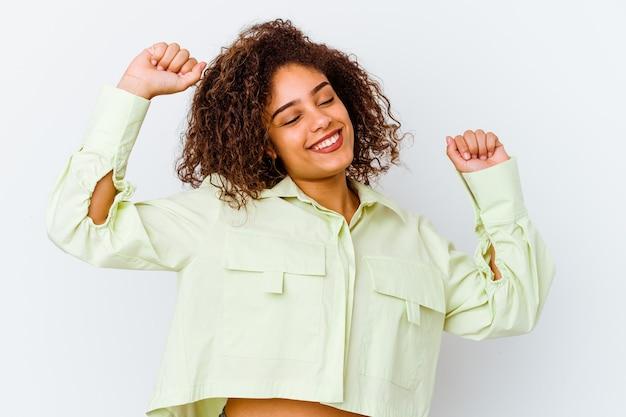 Jonge afrikaanse amerikaanse vrouw die op wit wordt geïsoleerd dat een speciale dag viert, springt en heft wapens met energie op.