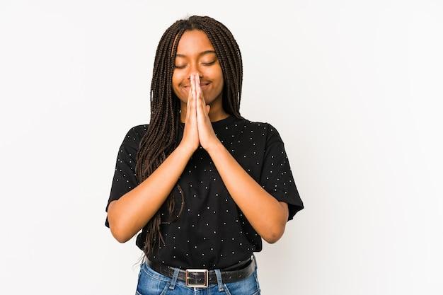 Jonge afrikaanse amerikaanse vrouw die op witte achtergrond wordt geïsoleerd die hand in hand bidt dichtbij mond, voelt zich zelfverzekerd.