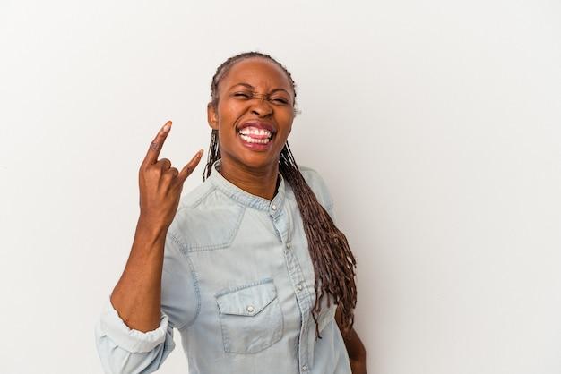 Jonge afrikaanse amerikaanse vrouw die op witte achtergrond wordt geïsoleerd die rotsgebaar met vingers toont