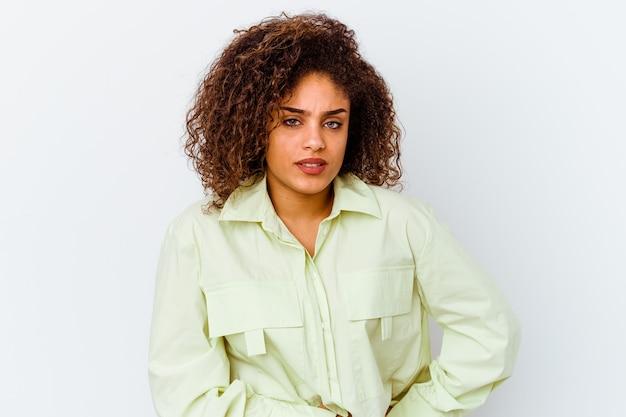 Jonge afrikaanse amerikaanse vrouw die op witte muur wordt geïsoleerd die leverpijn, buikpijn heeft