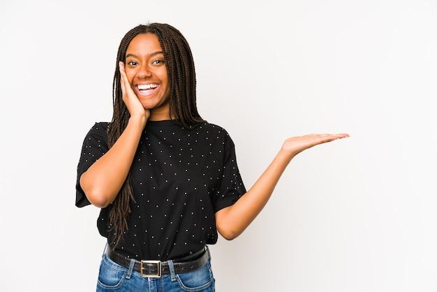 Jonge afrikaanse amerikaanse vrouw die op witte muur wordt geïsoleerd houdt exemplaarruimte op een palm, houdt hand over wang. verbaasd en opgetogen.