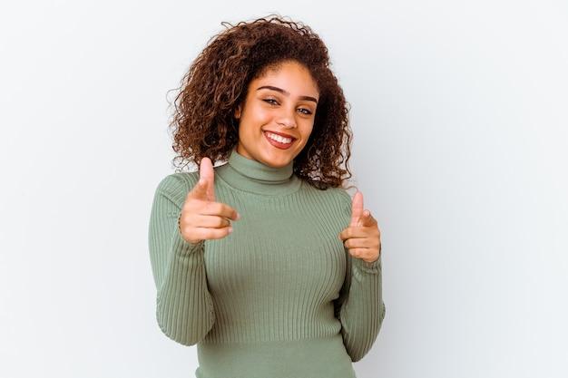 Jonge afrikaanse amerikaanse vrouw die op witte muur wordt geïsoleerd vrolijke glimlachen die naar voorzijde wijzen