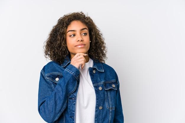 Jonge afrikaanse amerikaanse vrouw die opzij kijkt met twijfelachtige en sceptische uitdrukking.