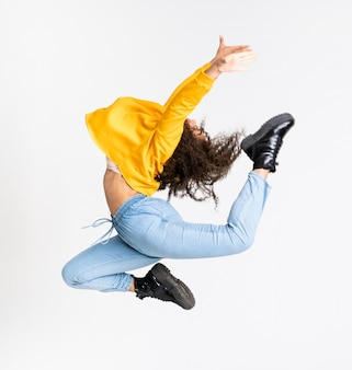 Jonge afrikaanse amerikaanse vrouw die over geïsoleerd wit danst