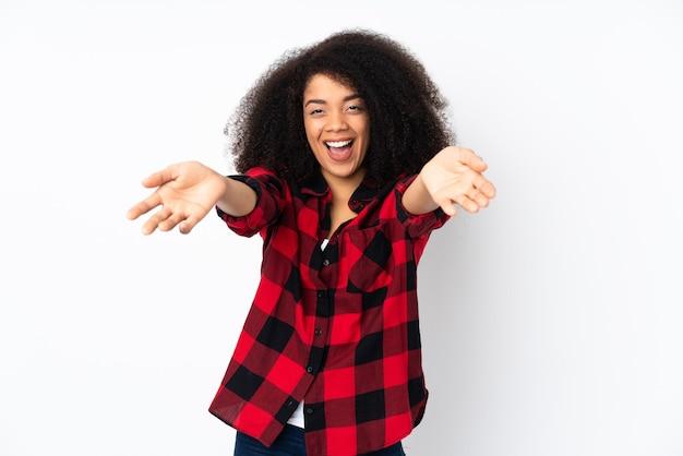 Jonge afrikaanse amerikaanse vrouw die presenteert en uitnodigt om met de hand te komen